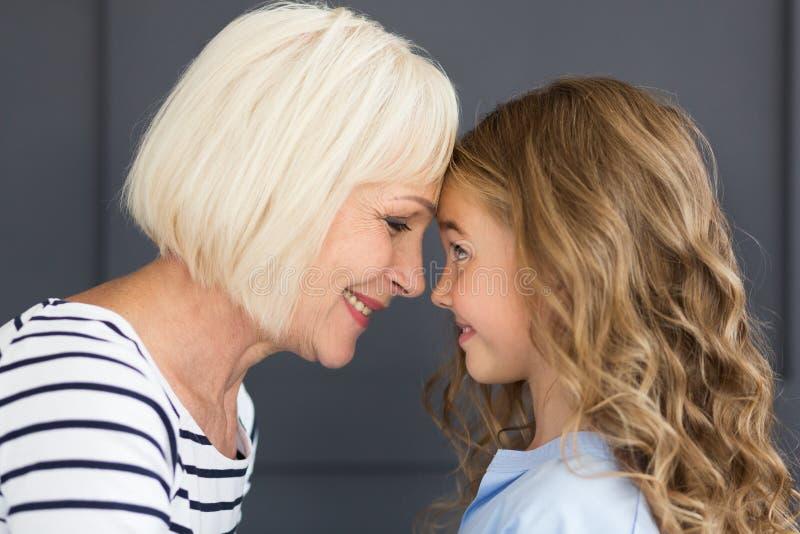 Mamie et petite-fille touchant leurs fronts, vue de côté image stock