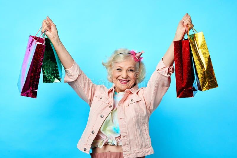 Mamie fraîche gaie avec la participation de bras augmentée beaucoup de sacs à provisions images stock