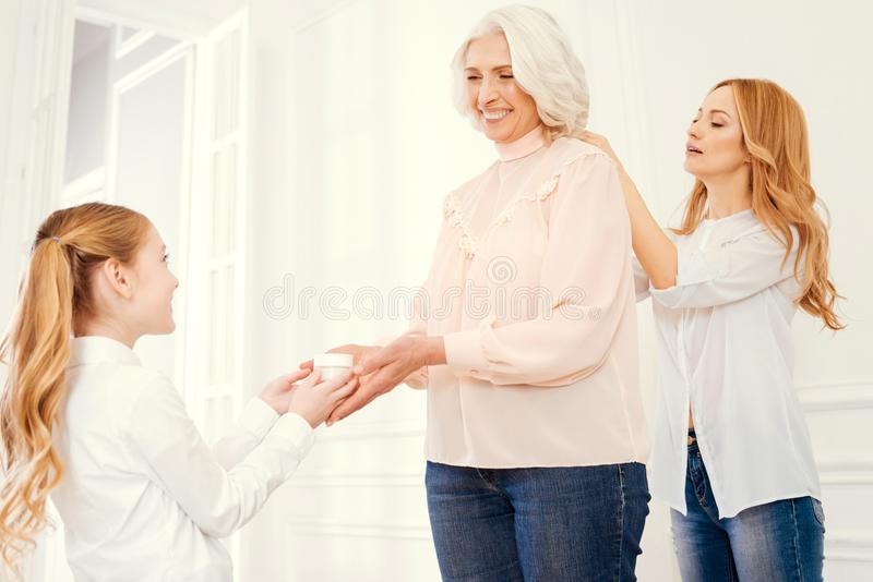Mamie rayonnante obtenant l'aide de la fille et de l'petit-enfant affectueux image stock