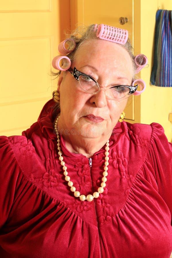 Mamie supérieure grincheuse avec des bigoudis  photographie stock