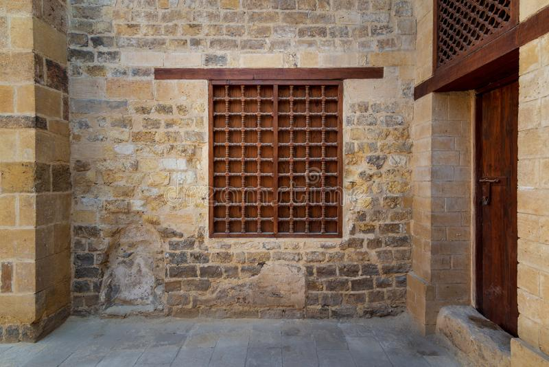 Mamluk era wooden closed window with wooden ornate grid over stone bricks wall, Medieval Cairo, Egypt. Mamluk era wooden closed window with wooden ornate grid stock photos
