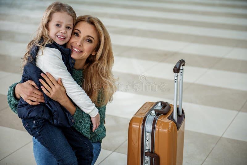 Mamma allegra e bambino che abbracciano all'aeroporto immagini stock libere da diritti
