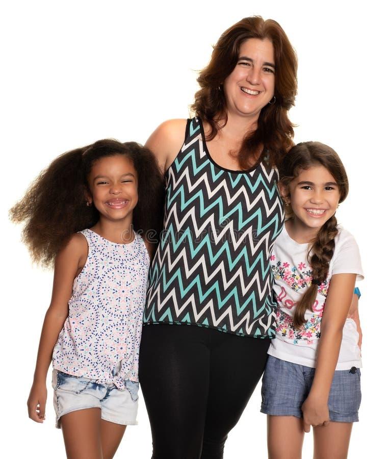 Mamma che abbraccia le sue figlie della corsa mista su un fondo bianco immagini stock libere da diritti