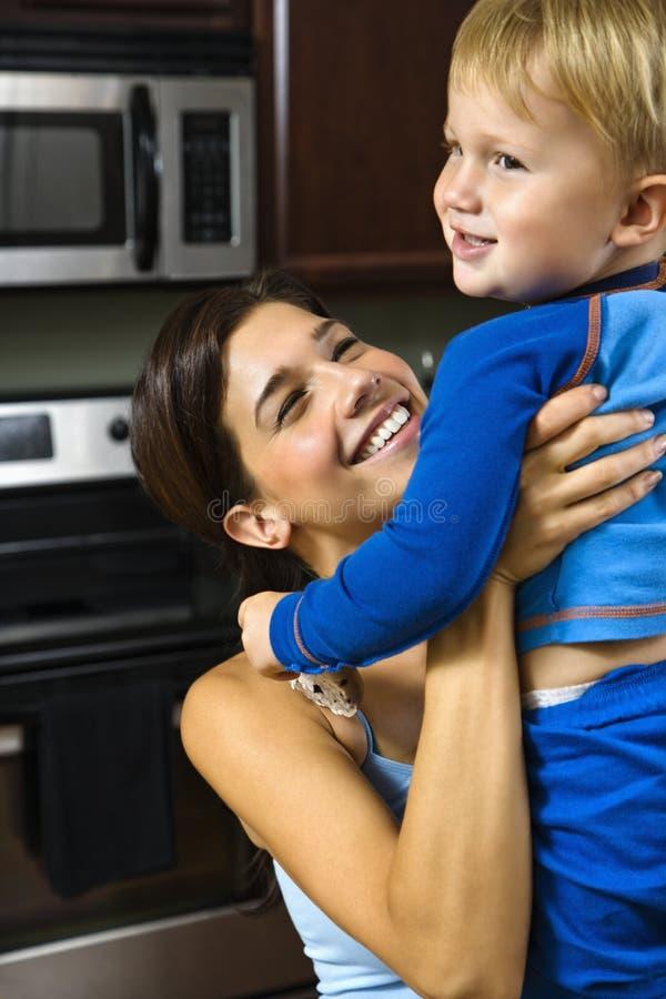 Mamma che alza bambino felice. immagini stock