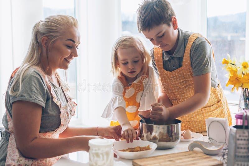 Mamma che cucina con i bambini sulla cucina fotografie stock libere da diritti
