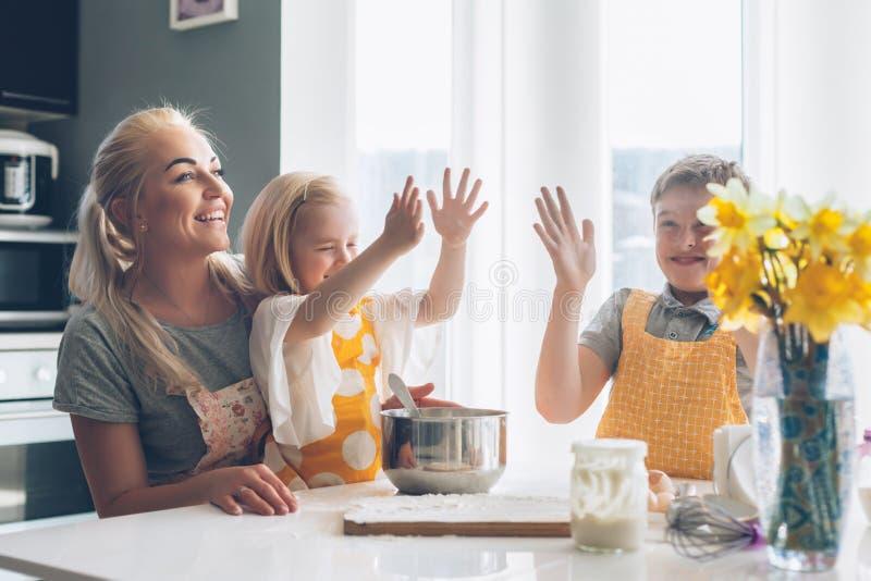 Mamma che cucina con i bambini sulla cucina fotografia stock libera da diritti