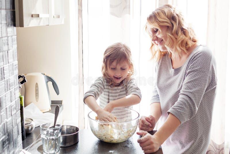 Mamma che cucina con la figlia immagini stock