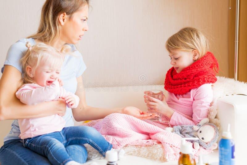 Mamma che dà alcune pillole al suo bambino malato fotografia stock libera da diritti