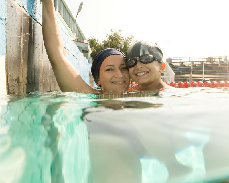 Mamma che dà a figlio una lezione di nuoto in stagno durante immagine stock