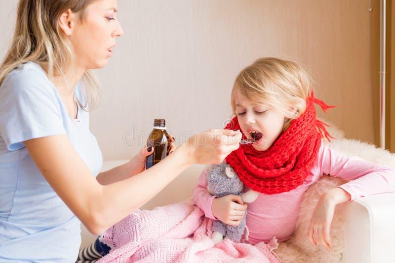 Mamma che dà sciroppo a sua figlia malata immagini stock libere da diritti
