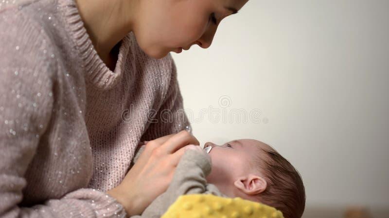 Mamma che d? a poco bambino adorabile gli accessori ortodontici dei bambini binky e neonati immagini stock