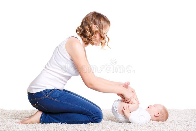Mamma che fa gli esercizi con il vostro bambino sul pavimento immagine stock