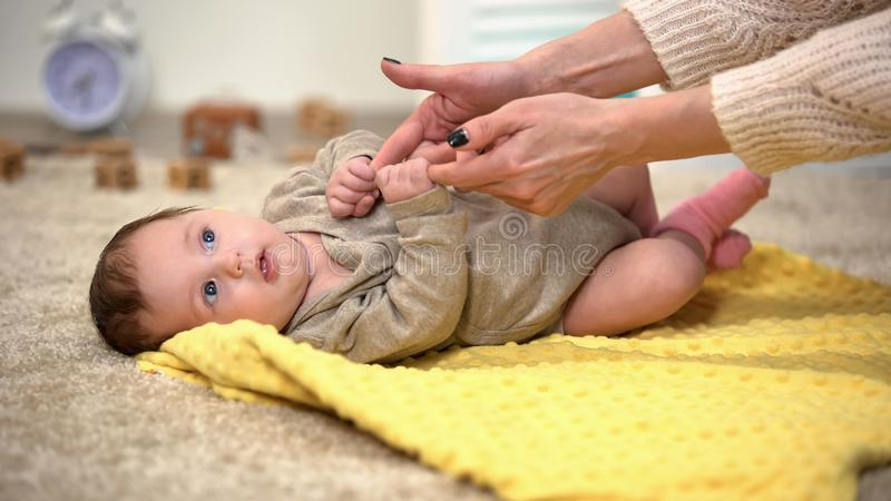 Mamma che gioca con la neonata affascinante, bambino che tiene le dita delle madri, tempo prezioso fotografia stock