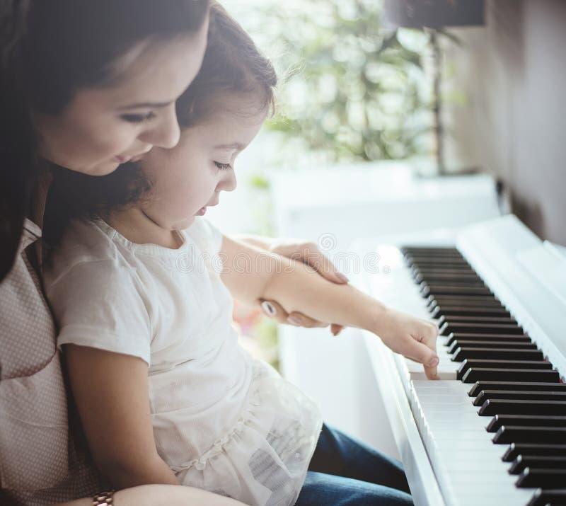Mamma che insegna al suo gioco del piano della figlia immagine stock