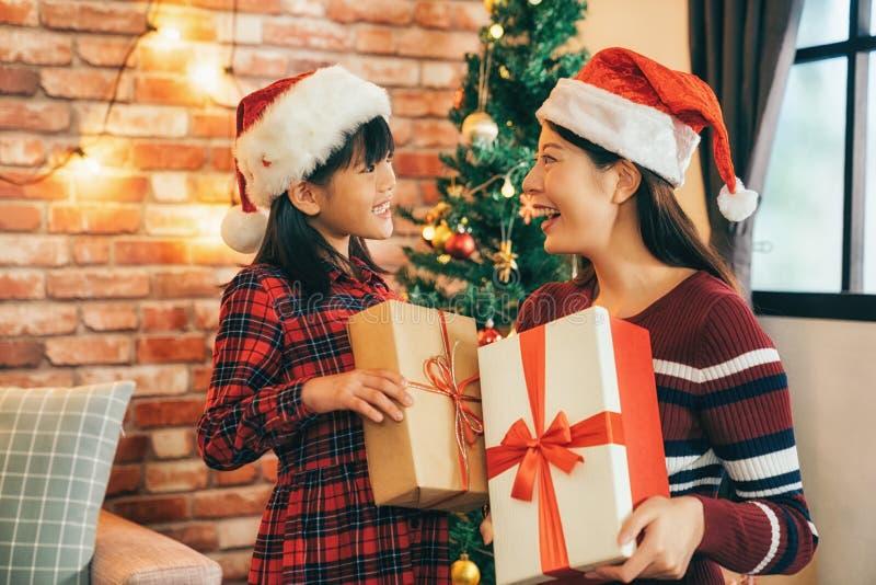Mamma che invia regalo alla ragazza di natale a casa fotografie stock libere da diritti