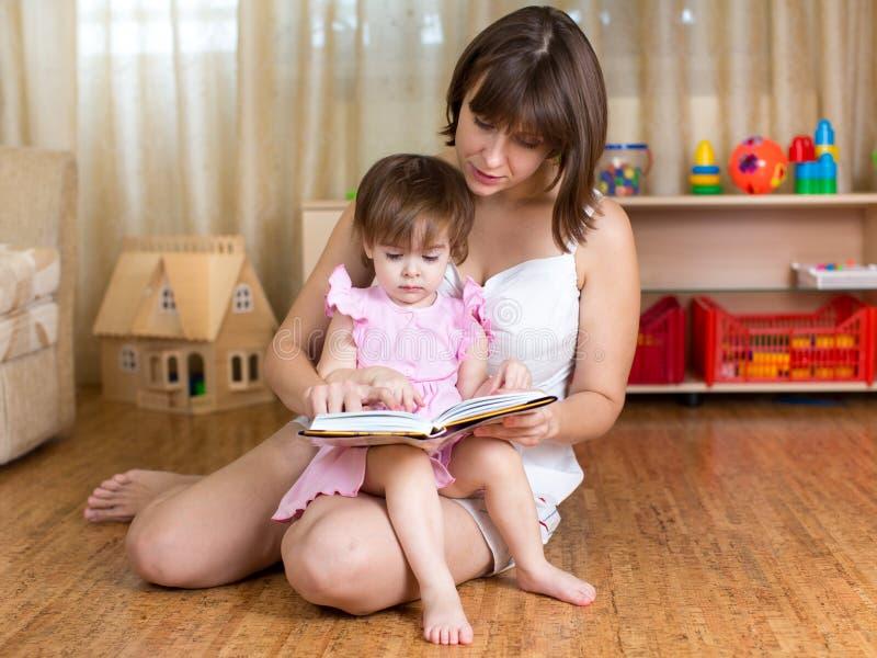 Mamma che legge un libro per scherzare a casa immagini stock