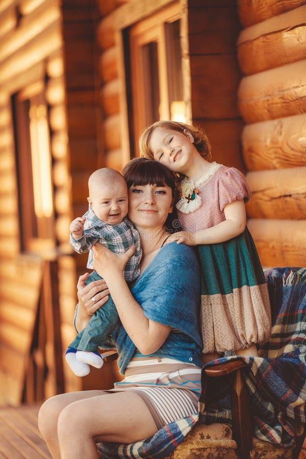 MAMMA con i bambini, sedentesi vicino ad una casa di legno fotografie stock libere da diritti