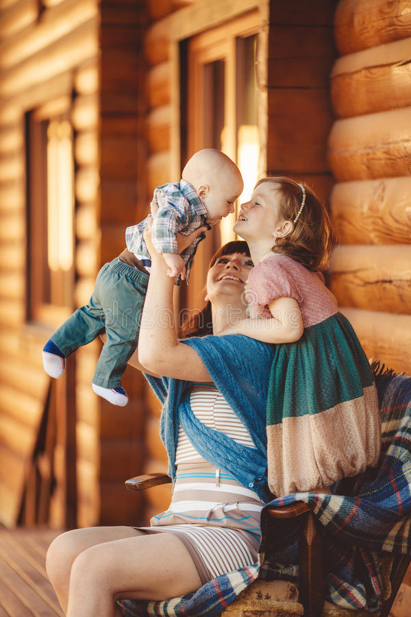 MAMMA con i bambini, sedentesi vicino ad una casa di legno immagine stock