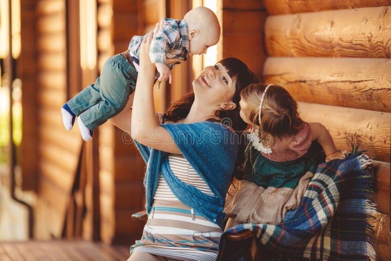 MAMMA con i bambini, sedentesi vicino ad una casa di legno immagini stock libere da diritti