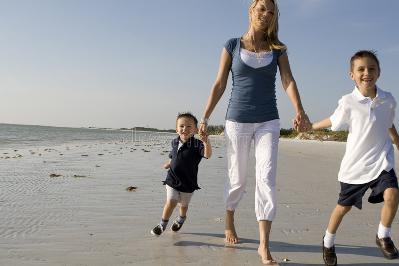 Mamma con i bambini su una spiaggia immagine stock