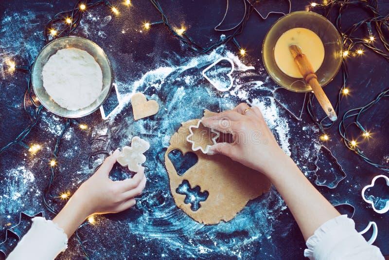 Mamma con la figlia che taglia i simboli di Natale nella pasta fotografia stock libera da diritti
