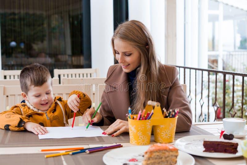 Mamma con le matite colorate tiraggio del ragazzo fotografia stock