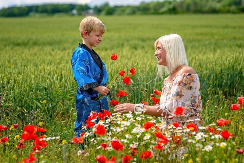Mamma con suo figlio in un prato magnifico Il ragazzo ha sorpreso sua madre con i papaveri rossi immagini stock libere da diritti