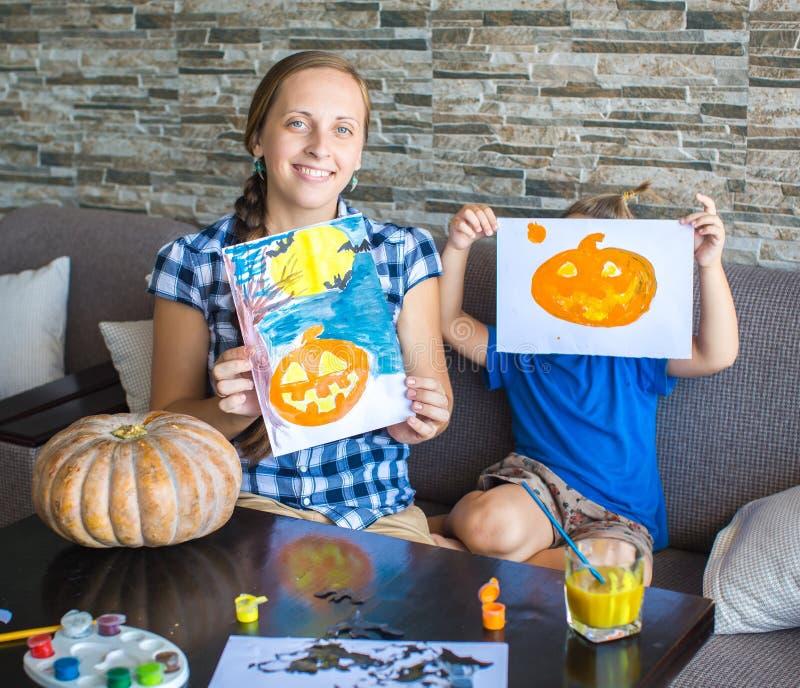 Mamma con tiraggio del figlio una zucca per Halloween fotografie stock libere da diritti