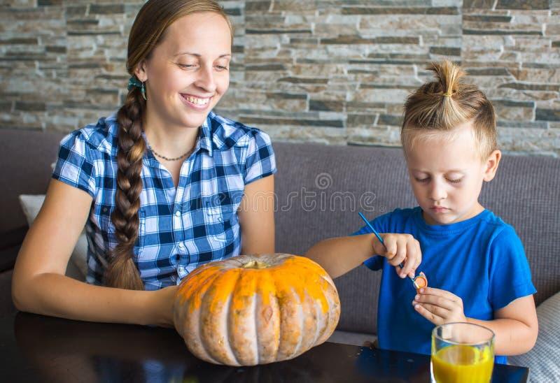 Mamma con tiraggio del figlio una zucca per Halloween immagini stock libere da diritti