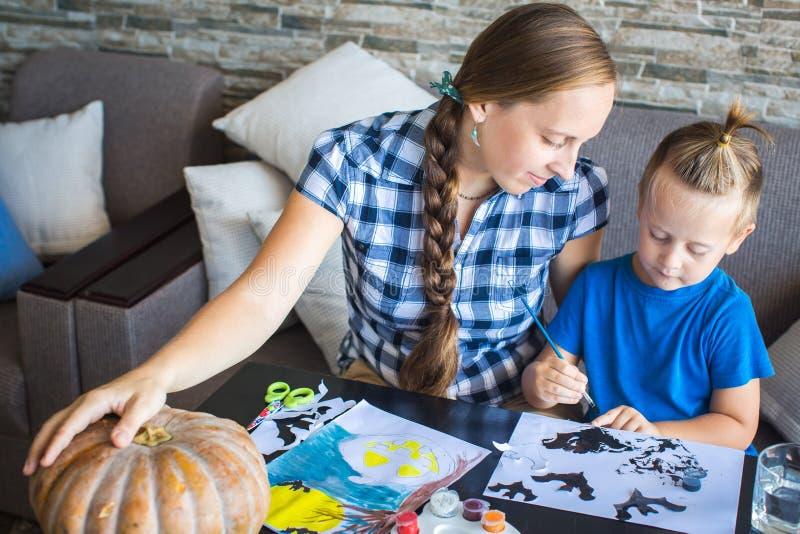 Mamma con tiraggio del figlio una zucca per Halloween fotografia stock
