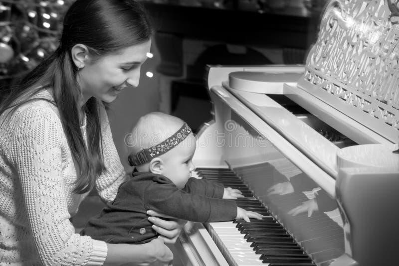 Mamma con un bambino vicino ad un piano bianco fotografia stock libera da diritti