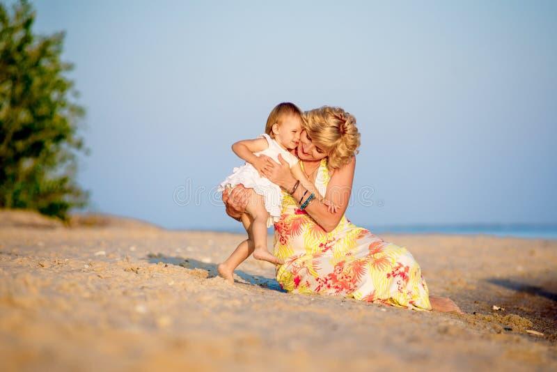 Mamma con una figlia che gioca sulla spiaggia immagini stock libere da diritti