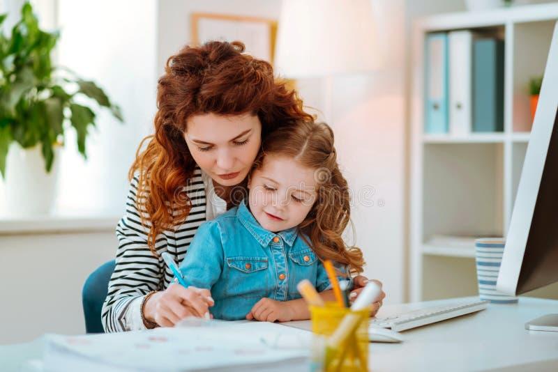 Mamma dai capelli rossi che aiuta la sue penna e scrittura di tenuta della bambina immagini stock