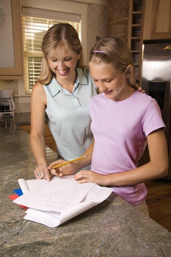 Mamma dat dochter met thuiswerk helpt. stock fotografie