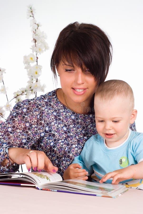 Mamma dat met baby wordt gelezen stock foto's
