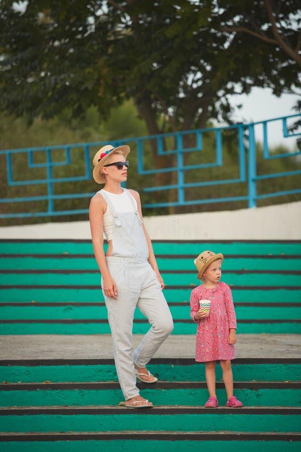 Mamma dei pantaloni a vita bassa in cappello di paglia con la figlia a piedi nudi Stile del film fotografia stock