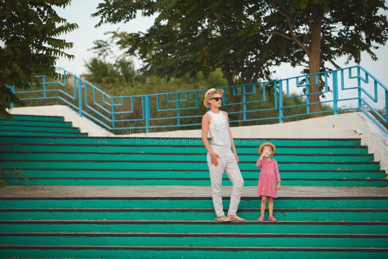 Mamma dei pantaloni a vita bassa in cappello di paglia con la figlia a piedi nudi Stile del film immagine stock libera da diritti