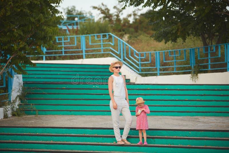 Mamma dei pantaloni a vita bassa in cappello di paglia con la figlia a piedi nudi Stile del film fotografie stock libere da diritti