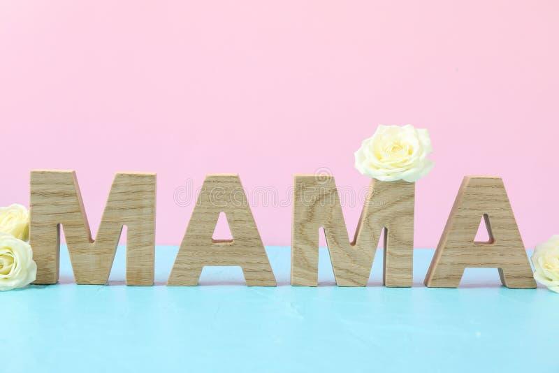 Mamma dell'iscrizione con le rose bianche sulla tavola blu contro il fondo di colore fotografie stock libere da diritti