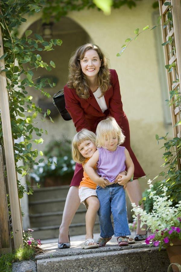 Mamma di funzionamento che porta i suoi bambini alla guardia fotografie stock libere da diritti