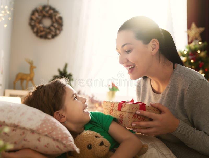 Mamma die Cristmas-gift voorbereiden aan dochter stock foto's