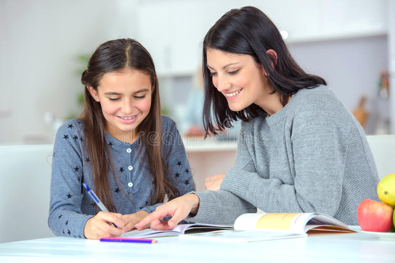 Mamma die daughter do homework helpen stock fotografie