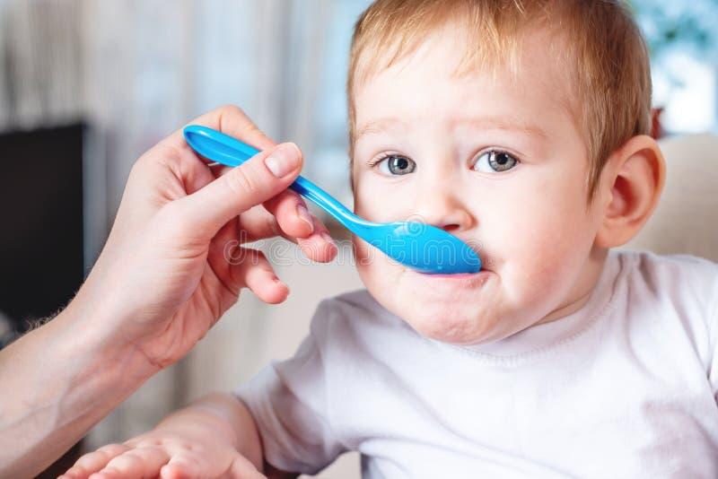 Mamma die de hand van de babyholding met een lepel van voedsel in de keuken voeden Gezonde babyvoeding stock afbeelding