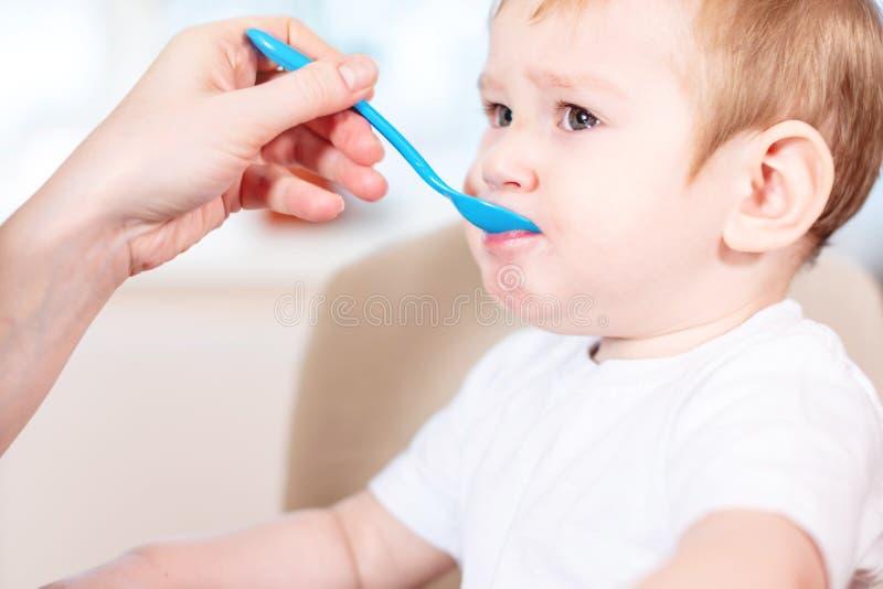 Mamma die de hand van de babyholding met een lepel van voedsel in de keuken voeden Gezonde babyvoeding royalty-vrije stock afbeeldingen