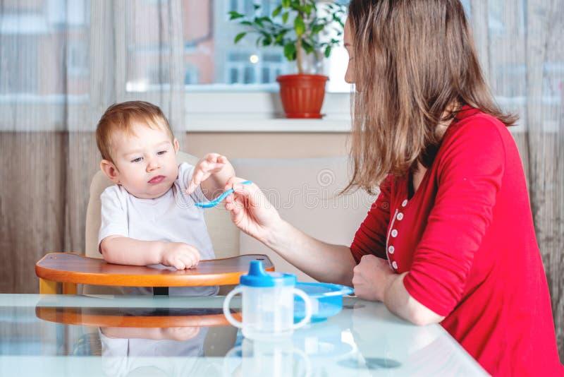 Mamma die de hand van de babyholding met een lepel van voedsel in de keuken voeden Gezonde babyvoeding Emoties van een kind stock foto's