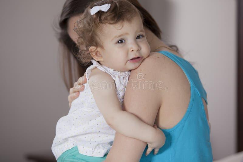 Mamma die haar babymeisje troosten royalty-vrije stock afbeelding