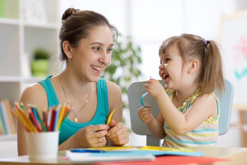 Mamma die haar kind helpen om gekleurd document te werken stock afbeelding