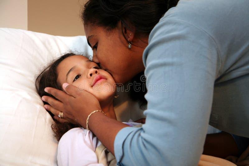Mamma, die Kind in Bett verstaut lizenzfreies stockfoto