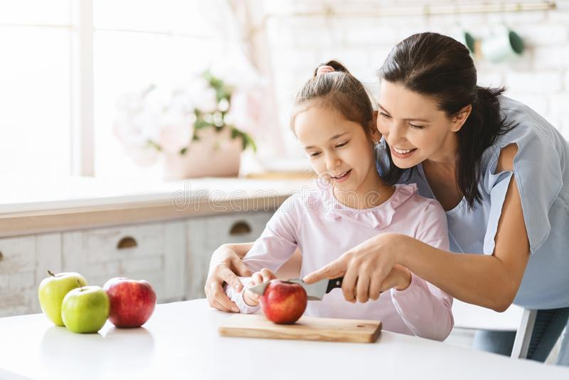 Mamma die Leuk Meisje onderwijzen om Apple met Mes te snijden royalty-vrije stock afbeeldingen