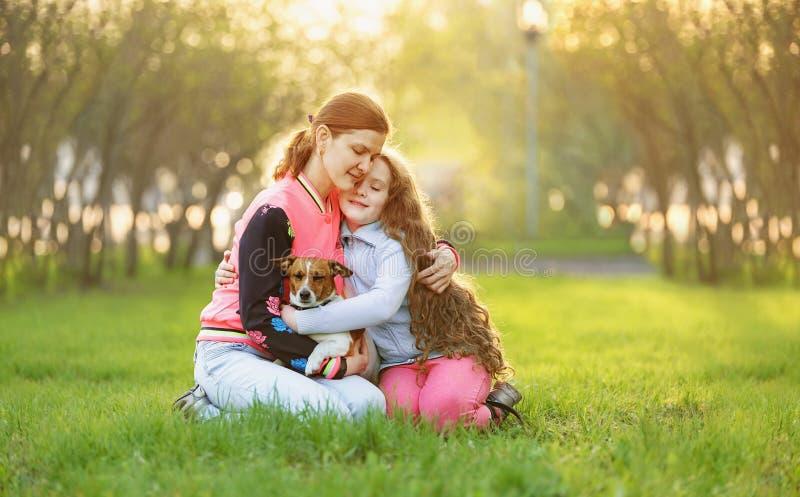 Mamma die met haar dochter en hond in het de lentepark koesteren royalty-vrije stock afbeeldingen